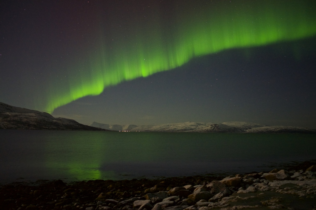 The northern lights dancing across the sky outside of Tromsø's city lights. Photo taken in Feb 2013 by This World Traveled