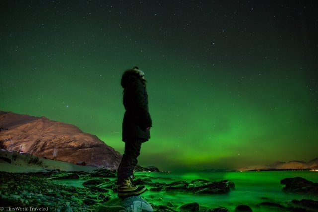 girl standing in from to the northern lights in norway