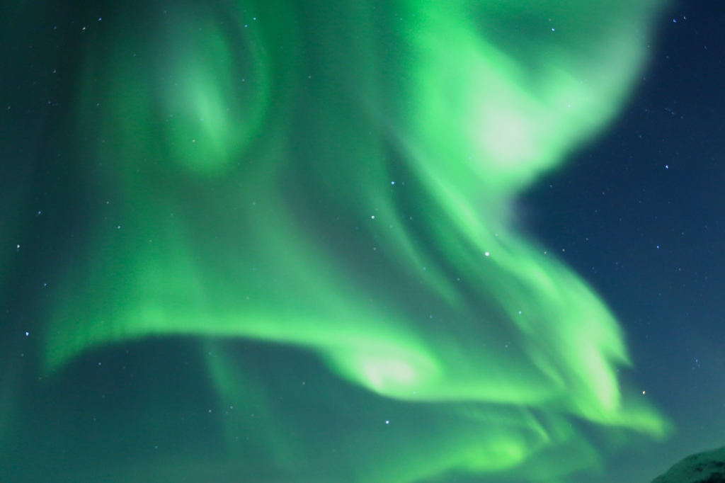 The northern lights dancing strongly in the sky above us in Norway