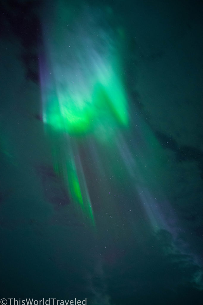 The beautiful colors of the aurora borealis peaking through the clouds near Tromsø, Norway