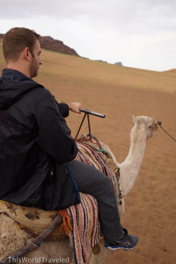 Jamin on his camel riding through the desert in Morocco