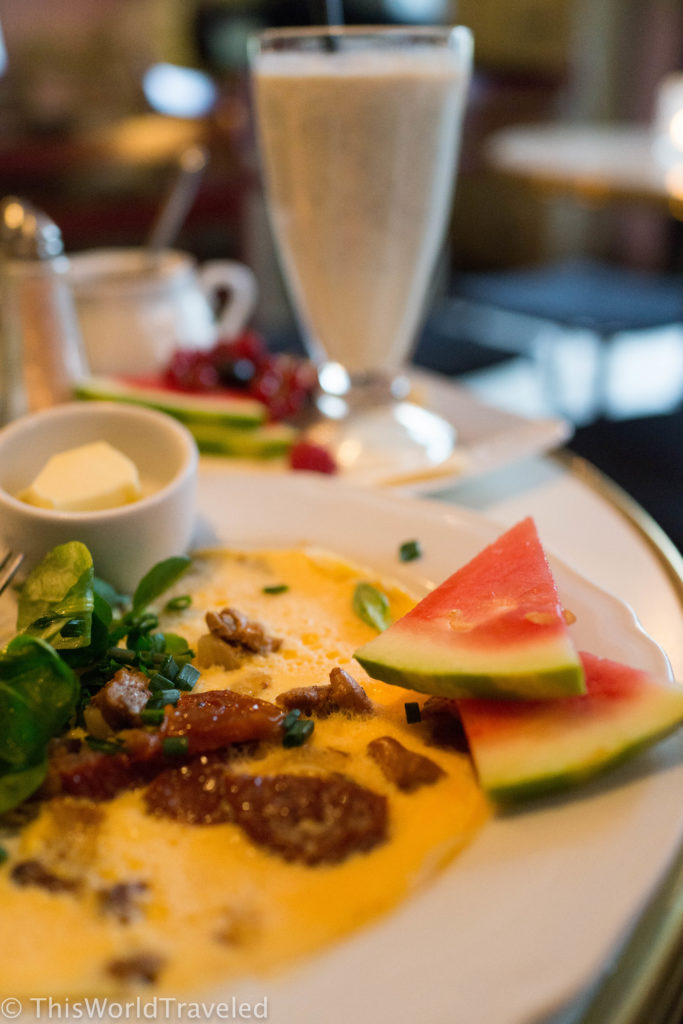 Omelet with sun-dried tomatoes and fresh fruit served at Camelot Cafe in Kraków