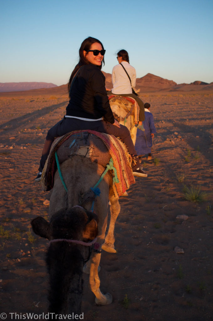 Marisa riding her camel at sunset in the Zagora desert in Morocco