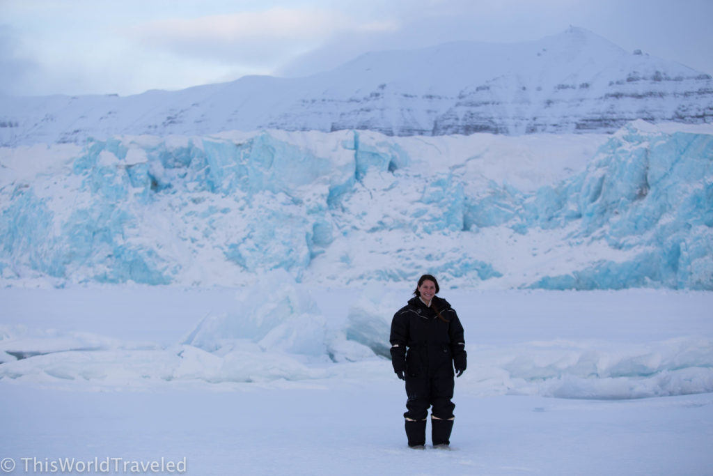 Girl standing in front of a glacier with thick clothing on in Svalbard
