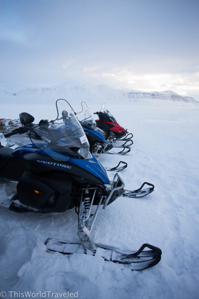 Blue and red snowmobiles parked on a glacier in Svalbard