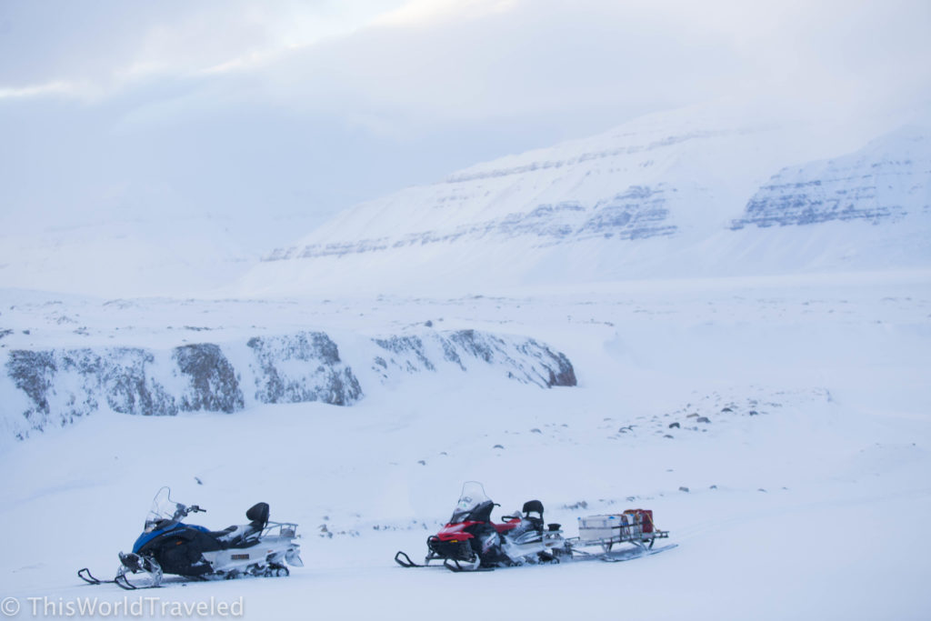 Snowmobiles parking in front of a glacier in Svalbard in the snow