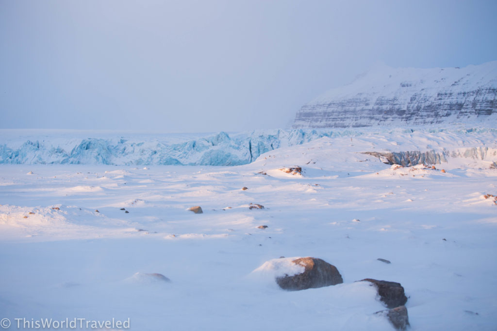 Snow covered rocks with a glacier in the back in Svalbard