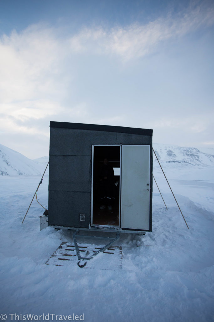 A small storage container house in the middle of snow in Svalbard