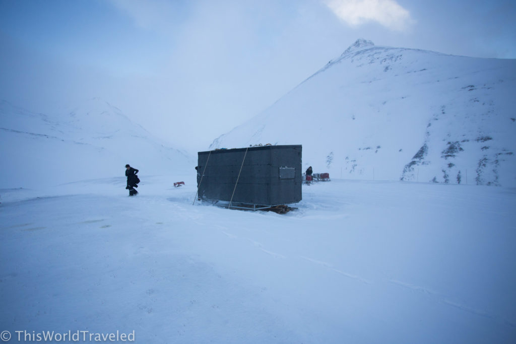 A small storage unit in the middle of a snowy glacier