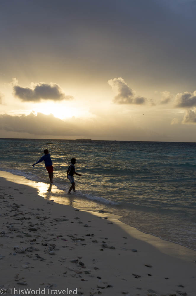 Local children playing on the beach of Mahibadhoo during sunset.