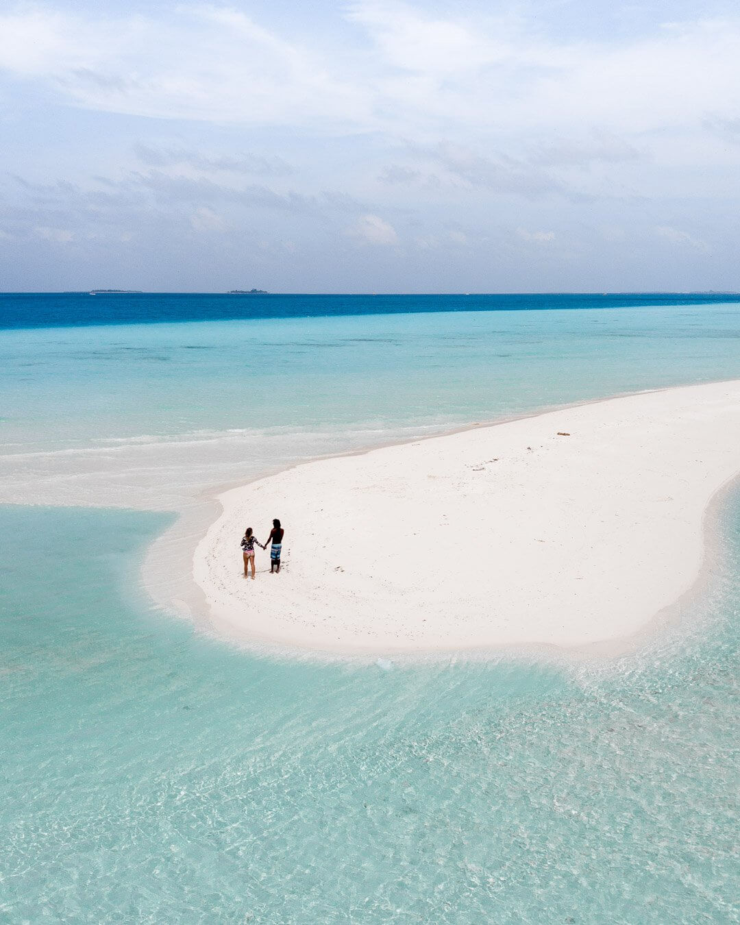 A guy and a girl on the end of a sandbank in the Maldives