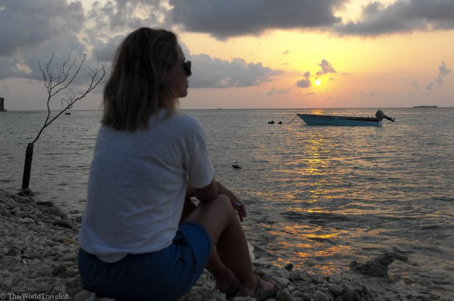 Girl watching the sunset on a local island in the Maldives