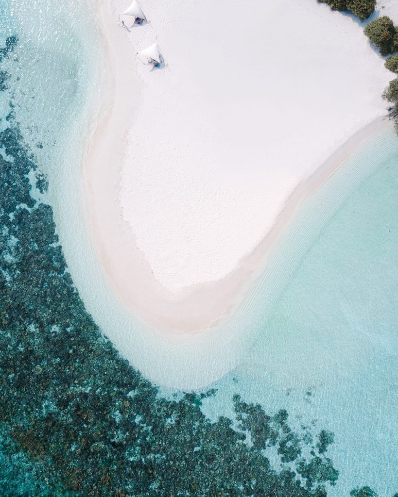 Drone shot of a uninhabited island in the Maldives with turquoise water and a coral reef