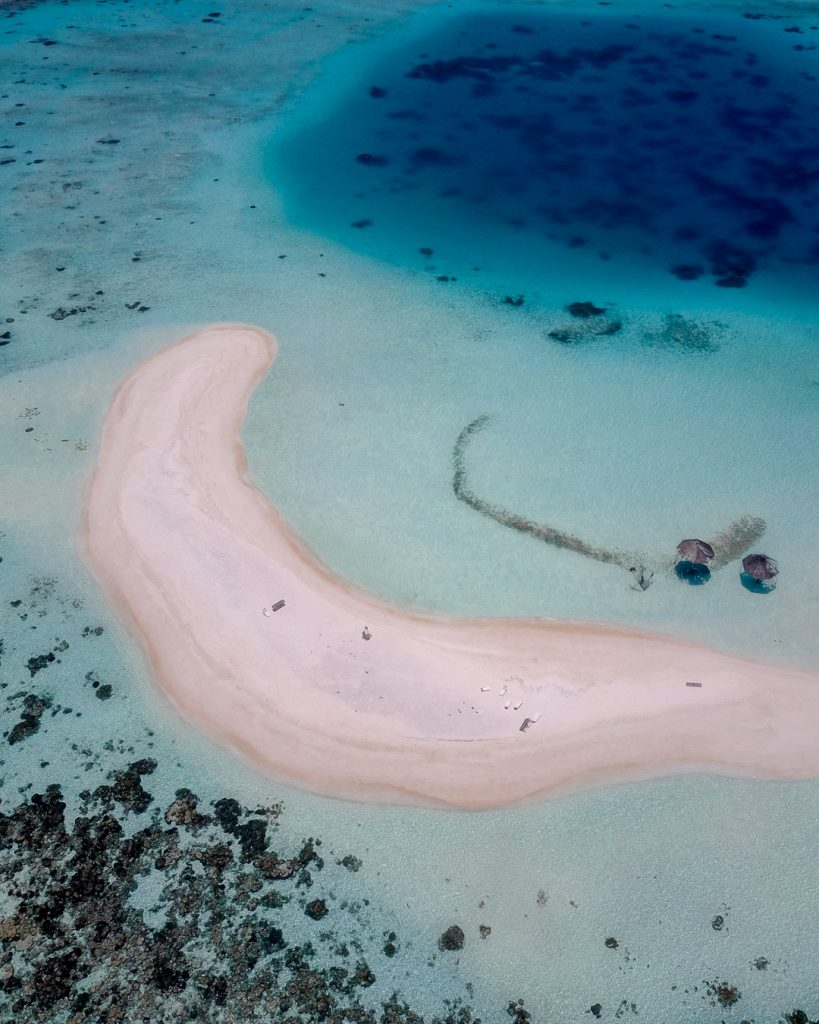Drone shot of a large sandbank in the Maldives with a coral reef and shades of turquoise