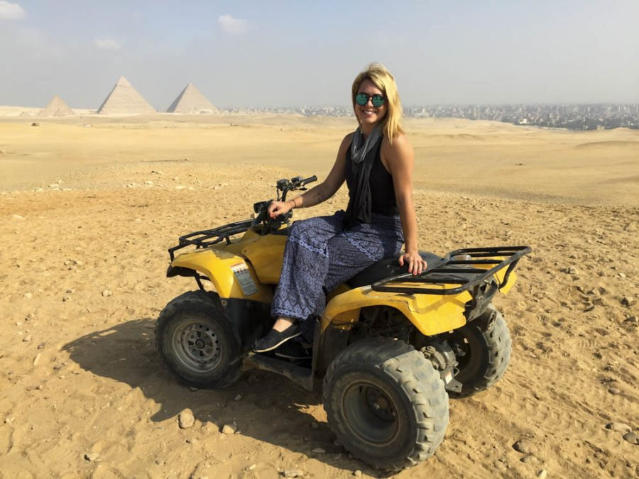 Girl riding a 4 wheeler in front of the Great Pyramids in Egypt