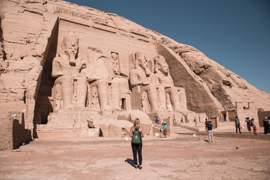 Girl standing in front of the statues at Abu Simbel in Aswan, Egypt