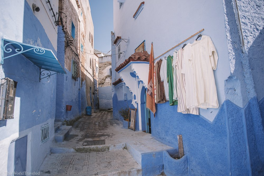 Freshly laundered clothes hang outside of the blue painted walls in Chefchaouen, Morocco
