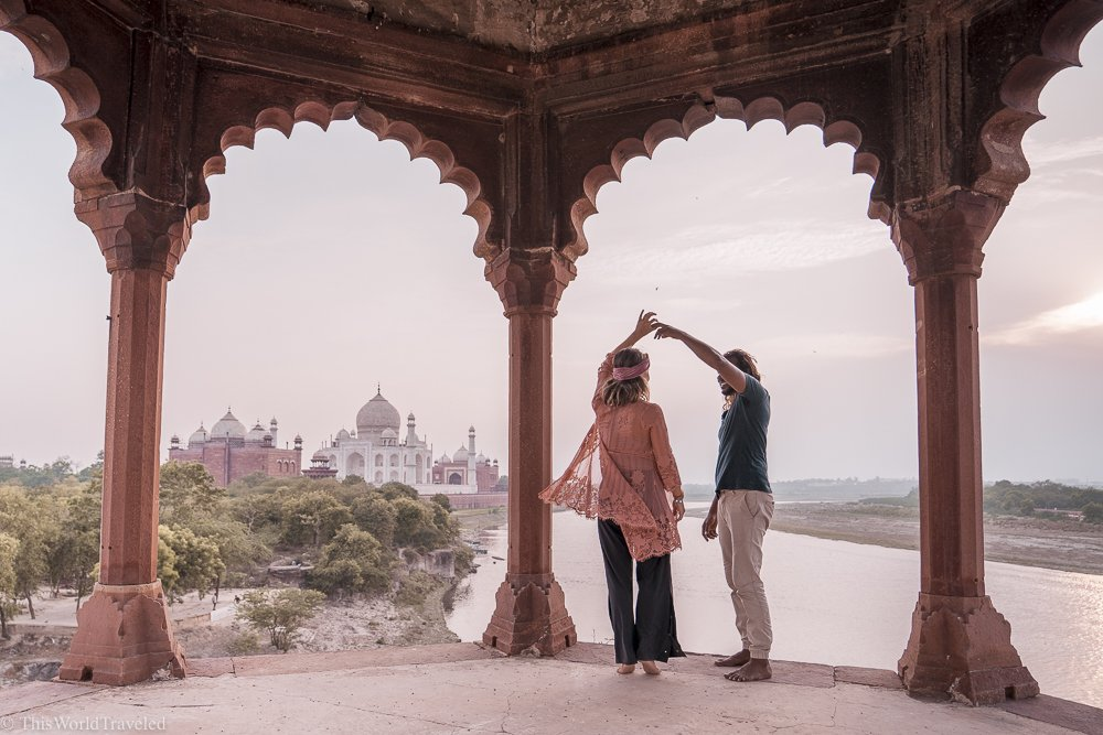 A guy and a girl twirling. There is a view of the Taj Mahal and a river behind them