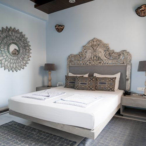 Hotel room with light blue walls and grey headboard