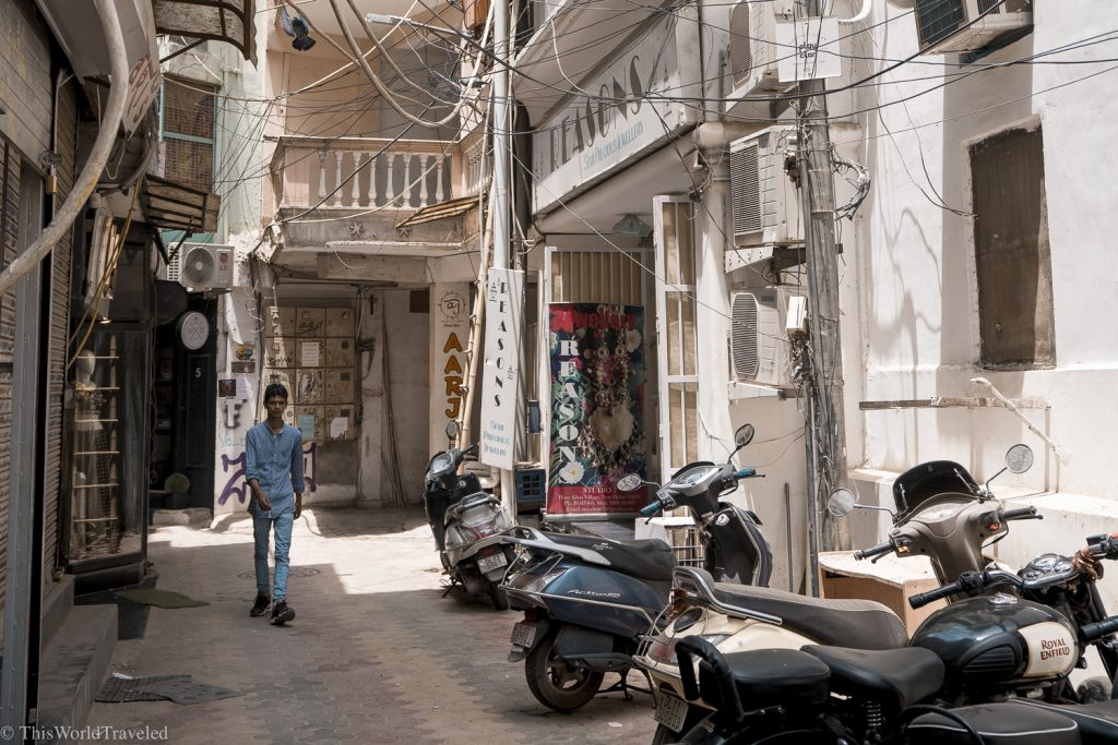 Narrow alley in Delhi, India with man walking and motorbikes lining the street. The buildings are painted white.