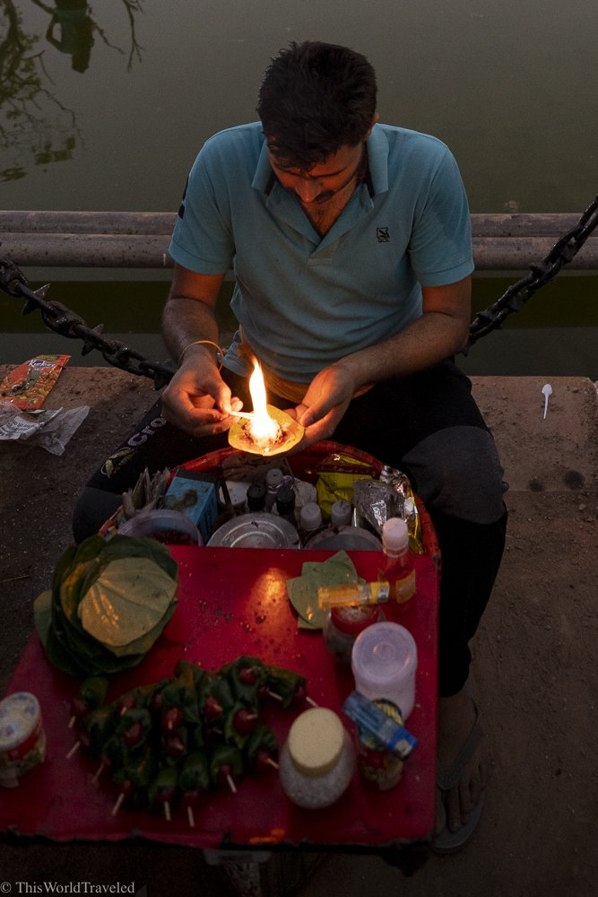 A man is lighting paan (a traditional after dinner treat) on fire and then selling it to people on the street
