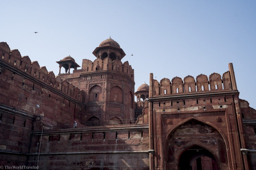 large red sandstone building located in Delhi, India. this is the red fort and was the residence for Mughal emperors for 200 years