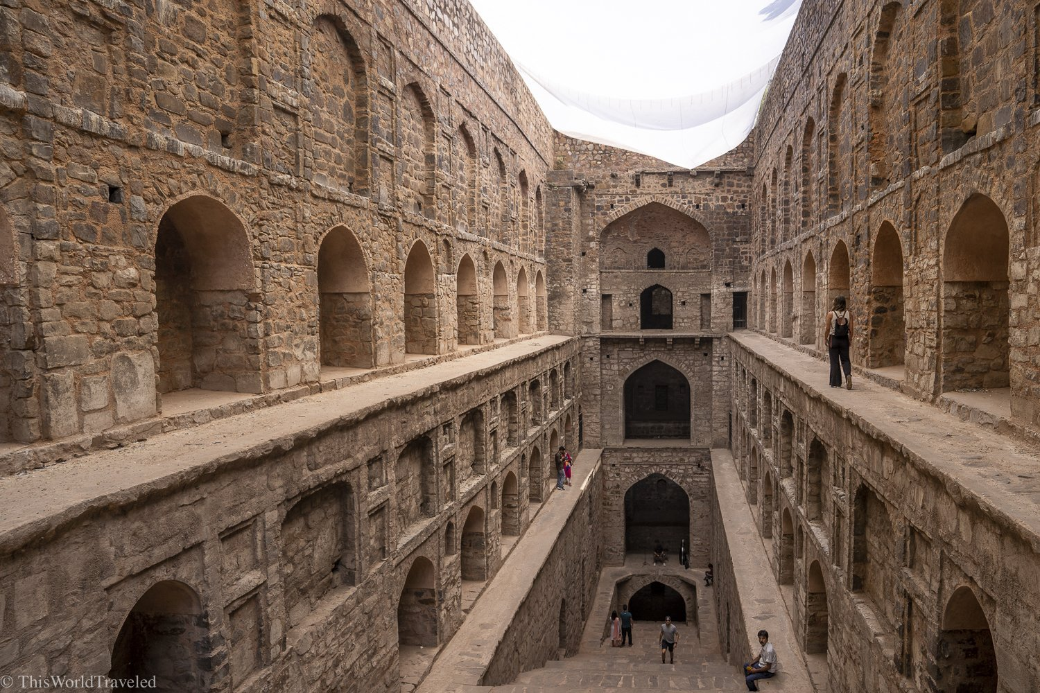 beige colored step well that is 3 stories deep. there are many archways and stairs leading down to the bottom. This is located in Delhi, India