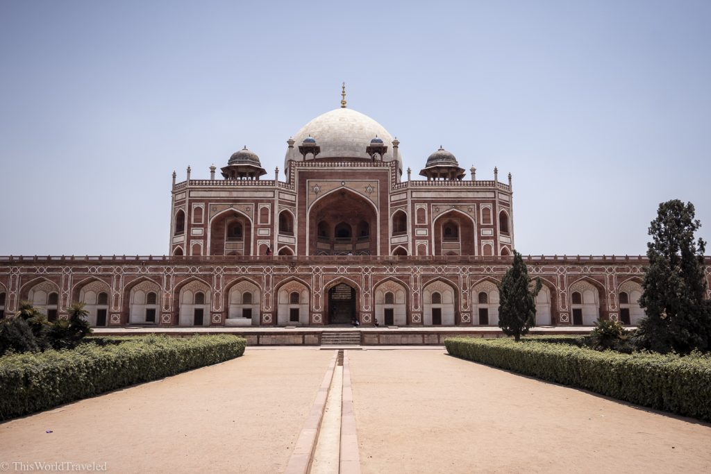 The main view of a large red and white building in India. The red is made from sandstone and the building has a large white dome on top.
