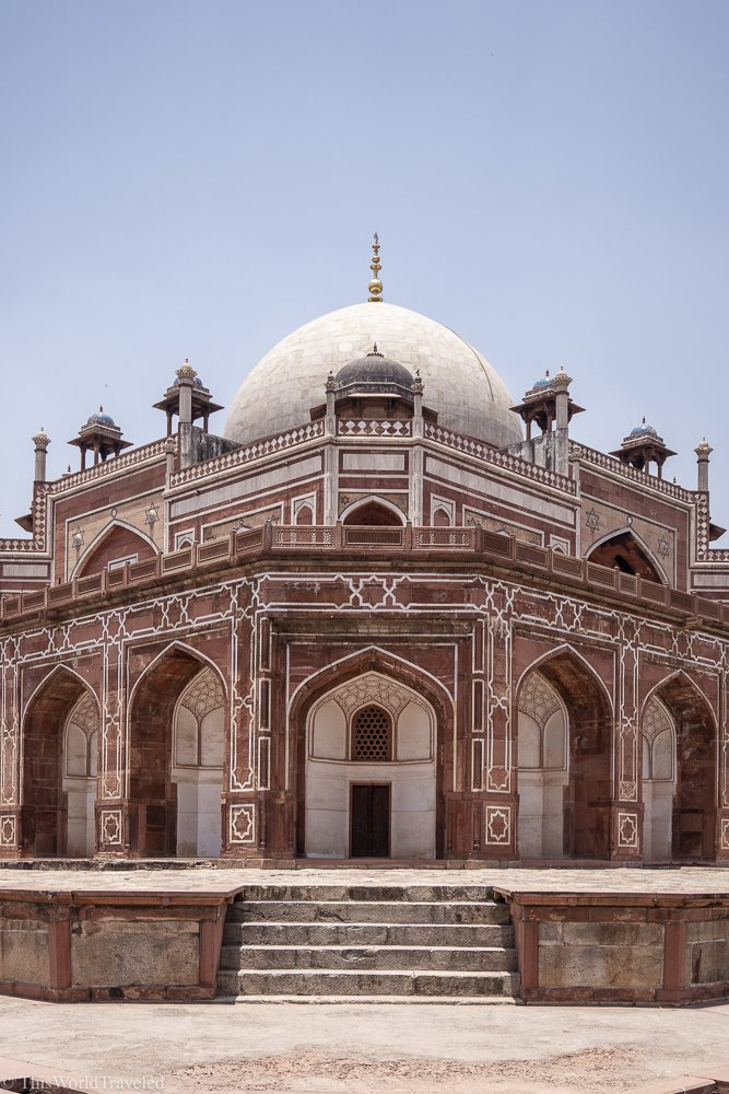Red and white sandstone building with a large white dome on top. The photo is taken at an angle.
