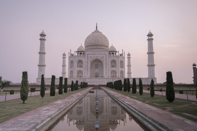 Sunrise at the Taj Mahal. Large white building with long reflections pool in front lined with trees