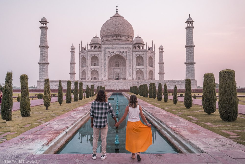 A couple holding hands standing in front of the Taj Mahal