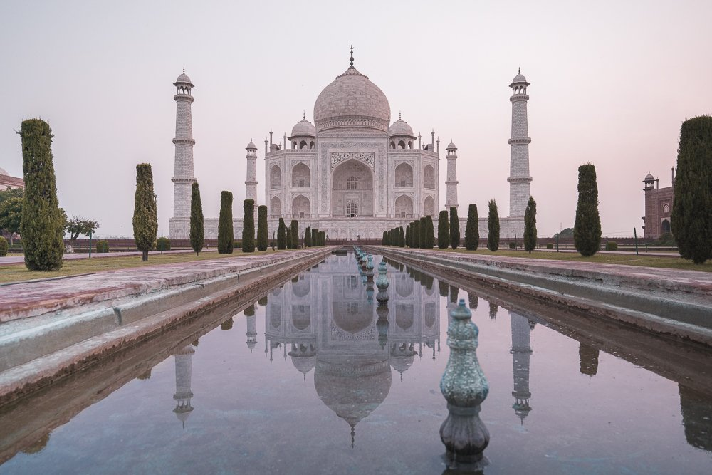 The Taj Mahal with the reflection pool in front and the sun rising in the back