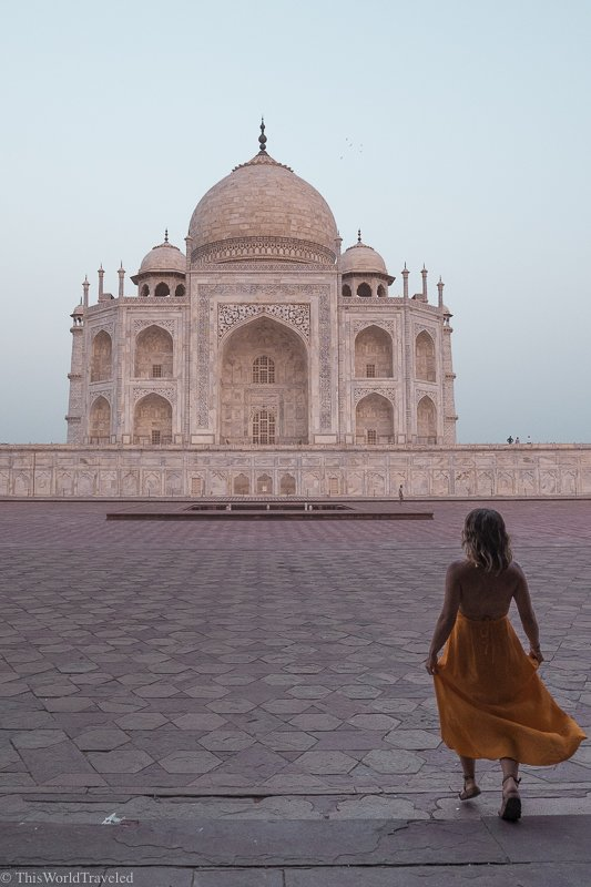 girl in yellow dress standing in front of the taj mahal at sunrise