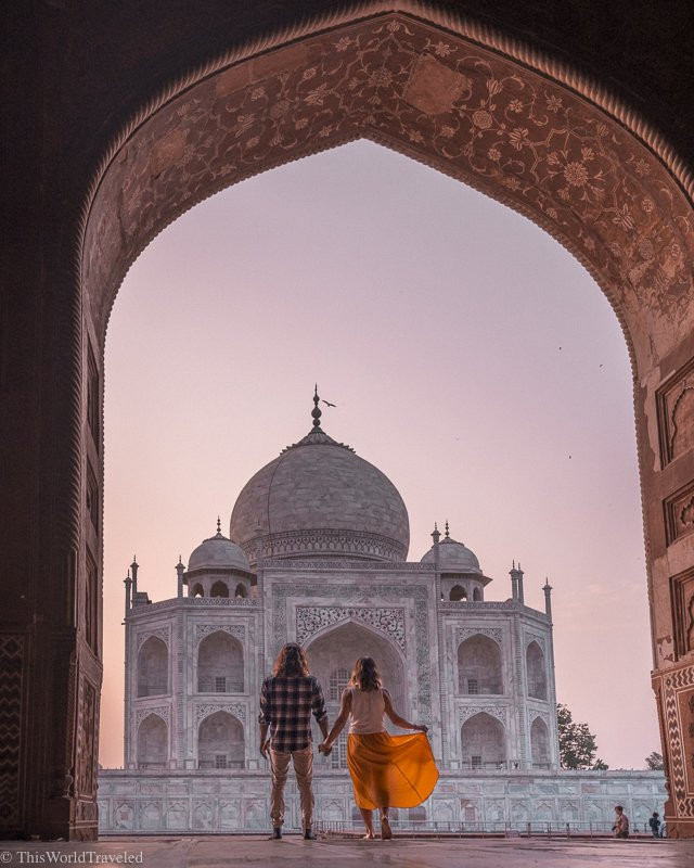Girl and guy holding hands standing in the archway and looking at the Taj Mahal