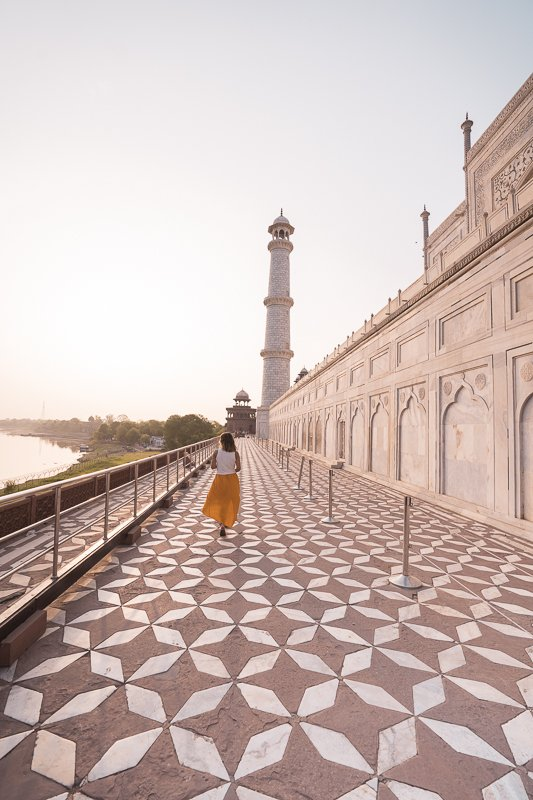 Girl in yellow skirt and white top walking along the side of the Taj Mahal with the river to the right