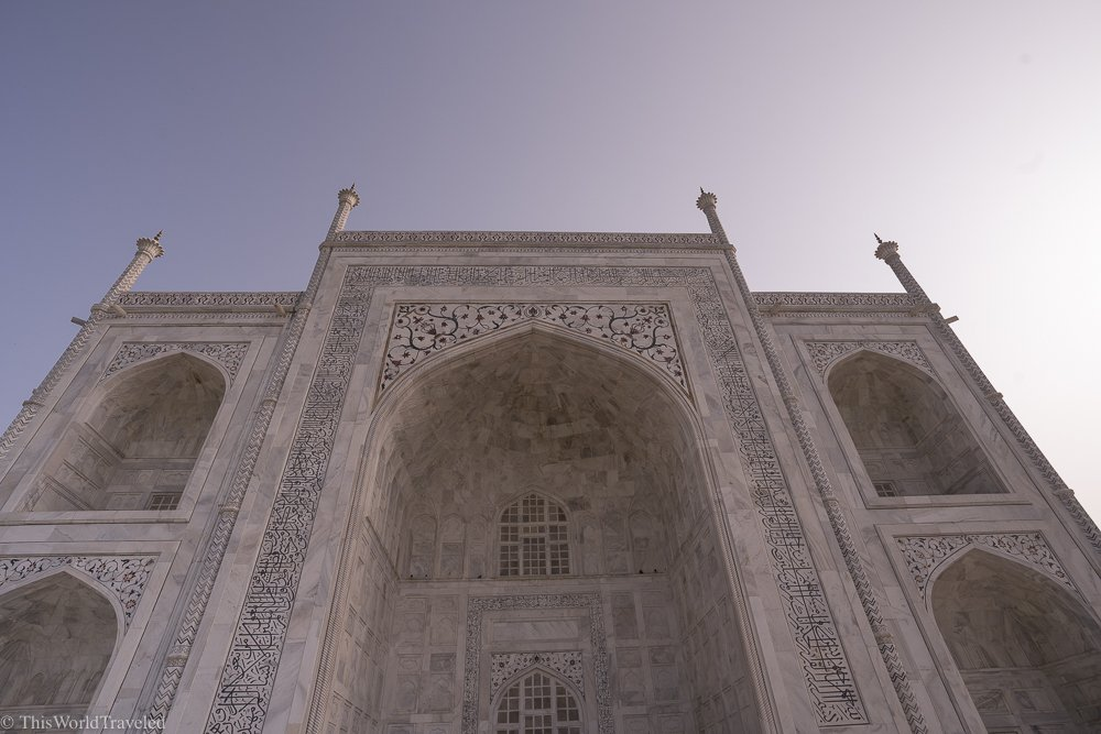 up close details of the taj mahal. The building is white marble inlaid with semi-precious stones