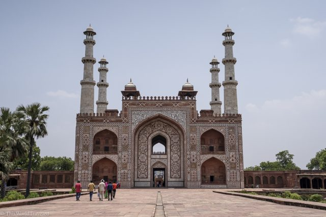 large red and white building with 4 large towers on top and is called the Tomb of Akbar in Agra, India