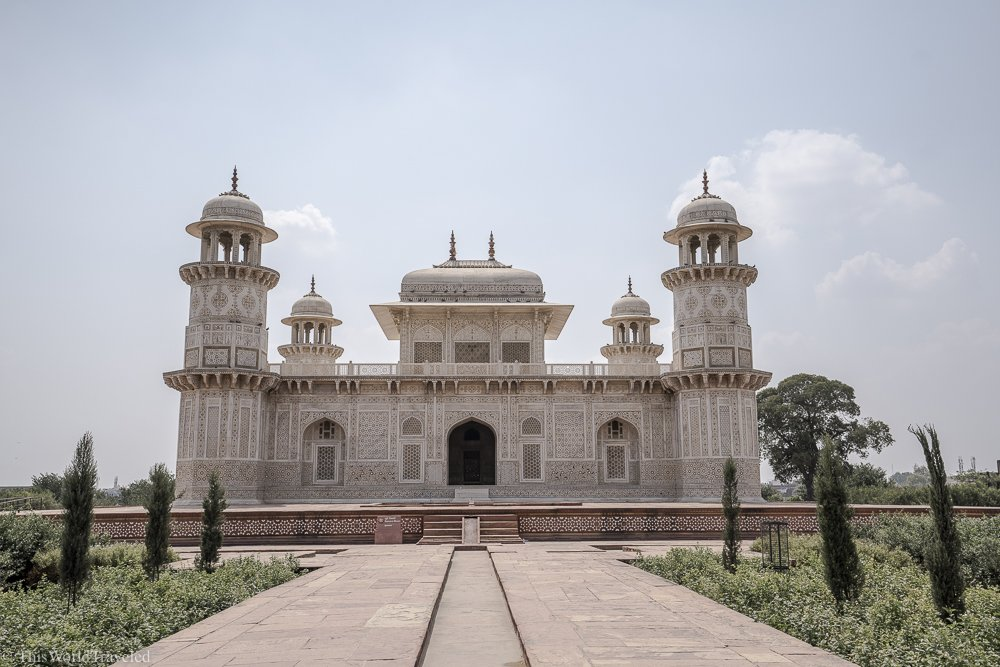Large white building with 4 large posts and domes located in Agra, India