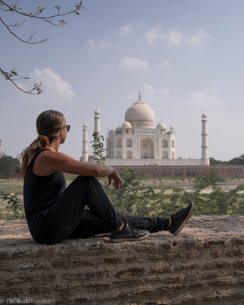 blonde girl in black outfit sitting on a ledge with a view of the Taj Mahal in India