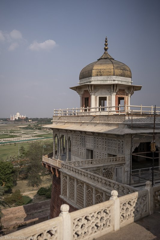 view of the taj mahal from inside the agra fort in India