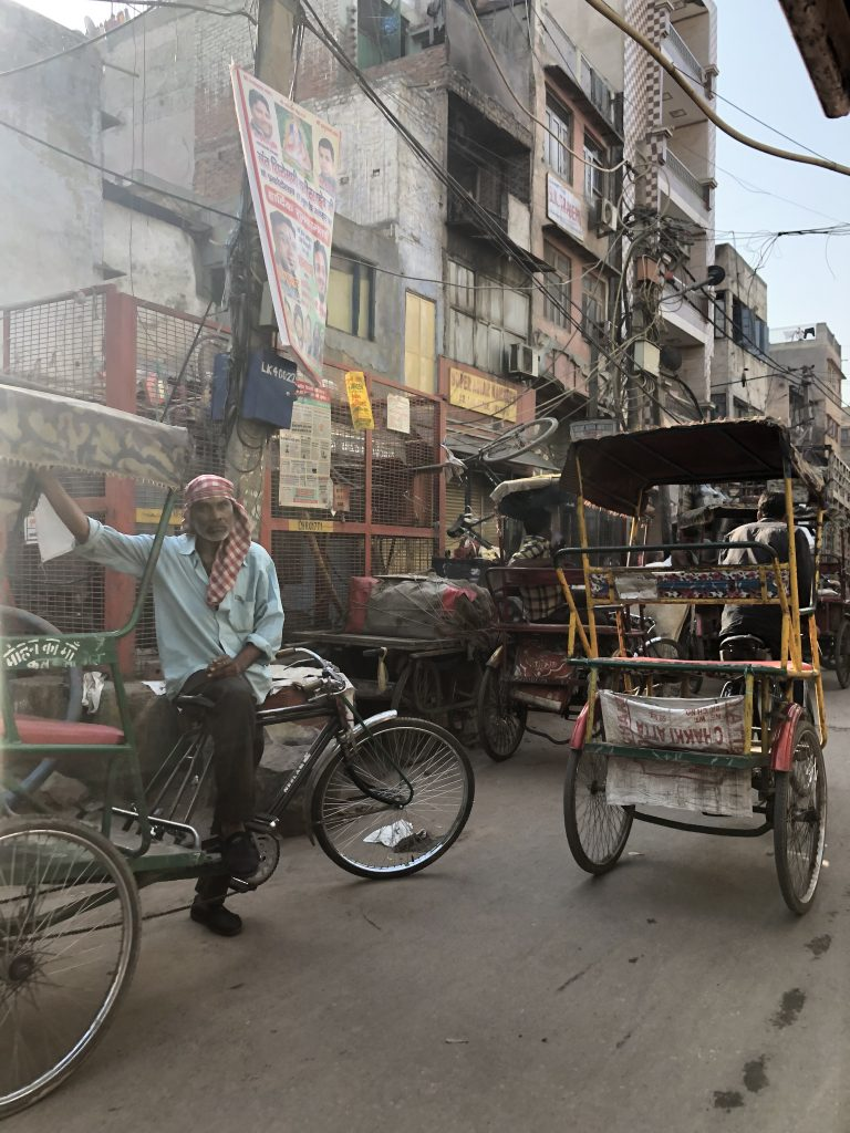 man sitting on a bike in the middle of a chaotic market in India