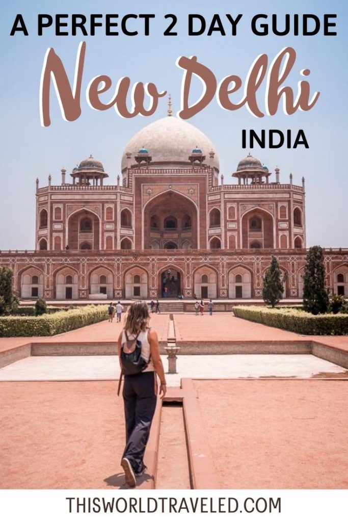 A girl in black pants standing in front of a large red, sandstone building with ornate details in Delhi, India