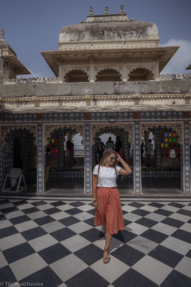 Girl in orange skirt walking in front of a structure in the City Palace