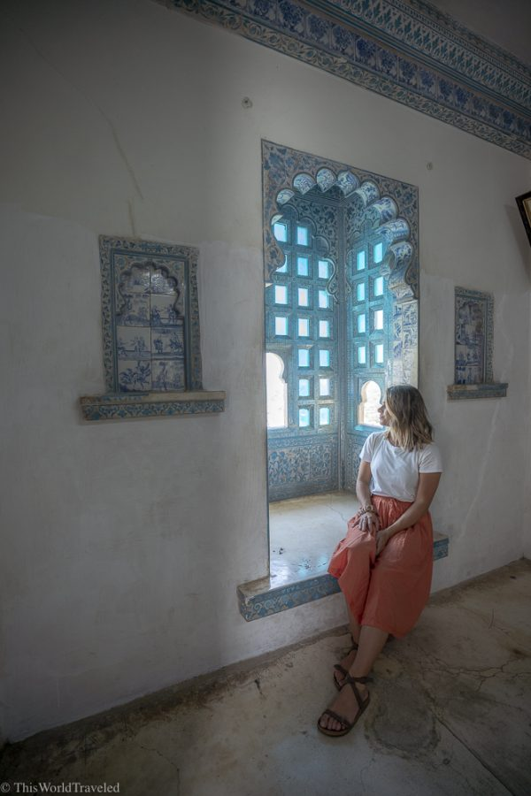 Girl in orange skirt sitting in a window with white walls and blue details