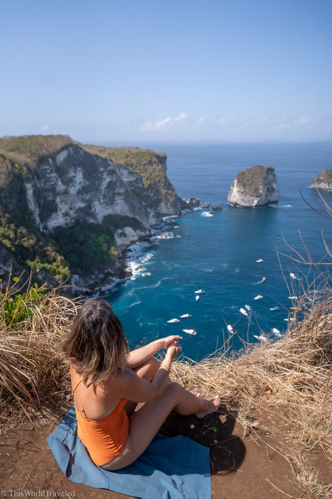 Girl in orange bathing suit sitting on a cliff overlooking the ocean