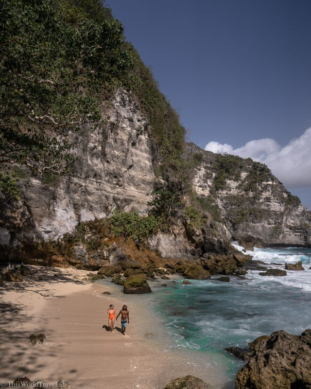 A guy and a girl walking along the beach with cliffs in the back
