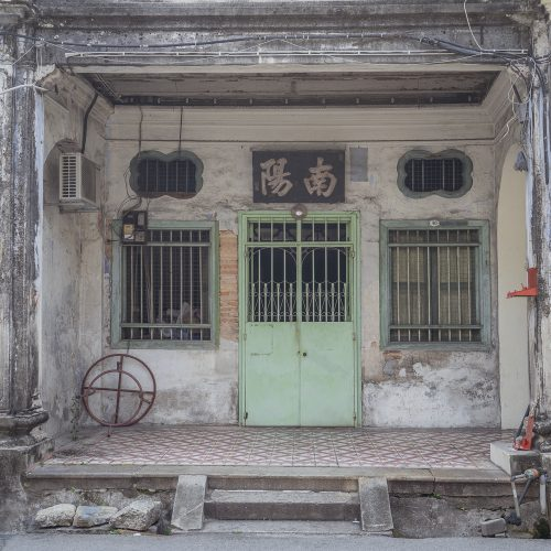 The exterior of a home in Georgetown, Penang with a mint green door and white walls
