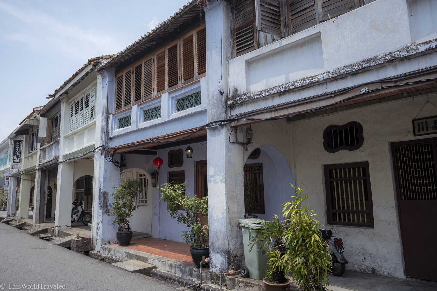 One of the streets in Penang with light blue walls and lanterns hanging
