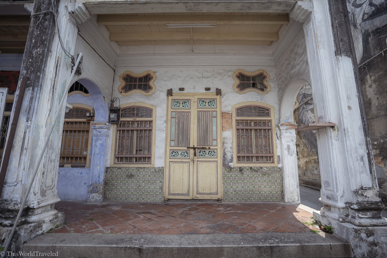 Door front in Penang with light yellow door and white walls
