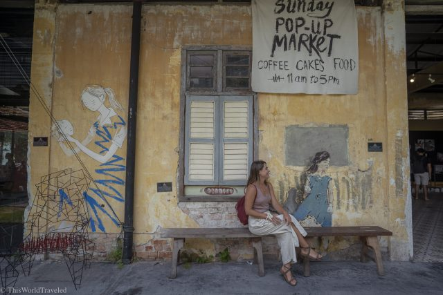 Girl sitting in front of the Hip Bus pop-up market sign in Penang